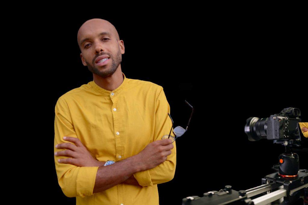 Man in long sleeve mustard shirt. DSLR camera on slider. Music videos.
