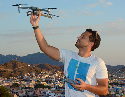 Man holds a drone. City in background. Mountains. Photography.