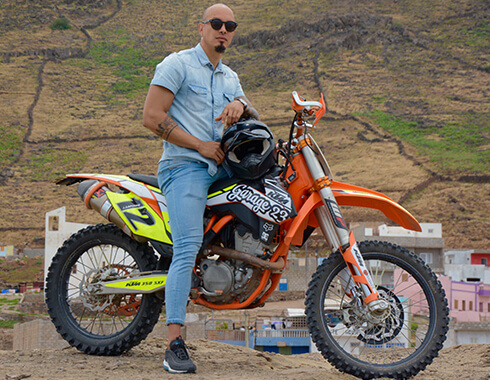 Man in jeans sits on off road dirt bike. Mountains. Photography.