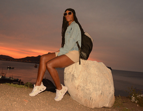 Woman sits on rock. Sunset. Backpack. Photography.