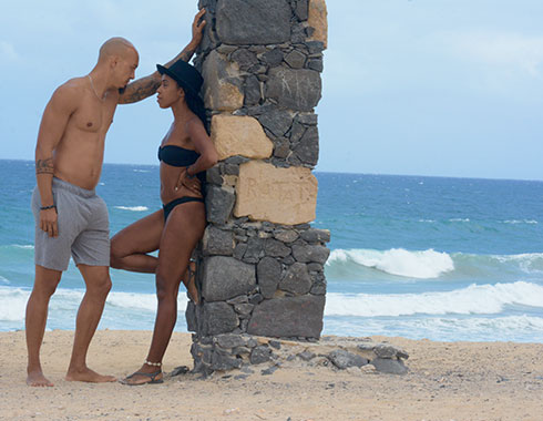 Man and woman lean on brick arch. Ocean. Sand. Photography.